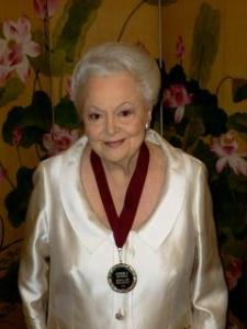 Olivia de Havilland wearing her Hubble Medal presented by the Cherry Blossom Committee of Marshfield, MO. This photo was used when her audio greeting was played at their event.