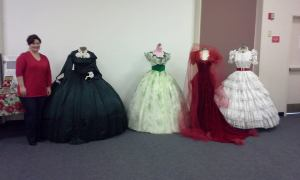 Nikki Luebke poses with the four dresses she brought for display.